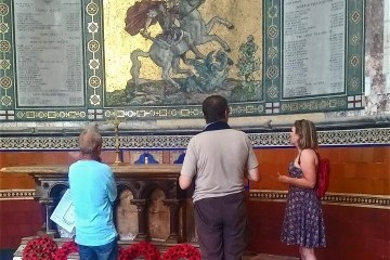 Our volunteer Derek shows 2 visitors the Chancel mural